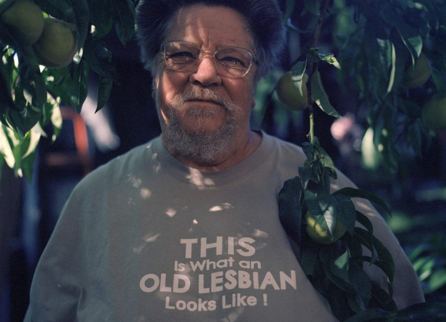 Portrait of the lesbian activist and author, Ardy Tibby, wearing a tshirt with the words 'This is what an old lesbian looks like!', taken by the artist, Louise Lever